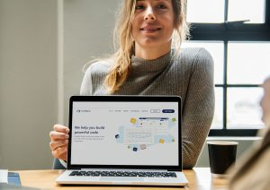 A women with a laptop screen showing the home page of codegrip